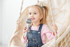 A little cheerful girl sings a song into the microphone. The con. Cept of childhood, performer, life style, music royalty free stock photography