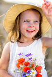 Little cheerful girl in a straw hat with wild flowers red poppy bouquet Royalty Free Stock Photography