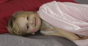 Little cheerful girl under a blanket on bed at home. Pretty, little girl royalty free stock images