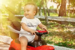 Portrait of a little cheerful baby in white shirt sitting half turned back on red push car in park or garden in sun rays royalty free stock image
