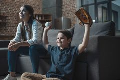 Little cheering boy with baseball mitt and ball sitting in living room with his mother and watching a game