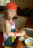 Little Chef. Wearing protective clothes, a proud little girl is helping her mother in the kitchen, brushing some pastries with some egg yolk Stock Photos