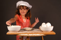 Little chef. A cute young girl mixing ingredients to make cookies,wearing a chefs hat and apron royalty free stock photography