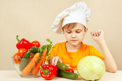 Little chef chooses vegetables for salad at table Stock Photos