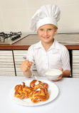 Little chef decorating cakes Stock Image
