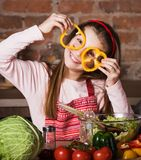 Little girl with sliced pepper Royalty Free Stock Image