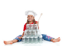 Little chef girl ready for the autumn canning. Little happy chef girl ready for the autumn canning of goods - sitting with lots of jars stock images