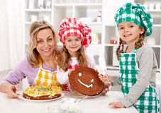 Little chef girls with their mother making a cake Royalty Free Stock Image