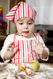 Little chef in the kitchen. Wearing an apron and headscarf,surprise looking at hatched chick Stock Images