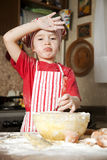 Little chef in the kitchen. Wearing an apron and headscarf Stock Photography