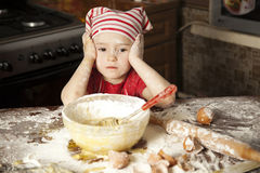 Little chef in the kitchen. Wearing an apron and headscarf Royalty Free Stock Photo