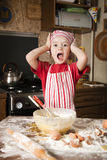 Little chef in the kitchen. Wearing an apron and headscarf Stock Images