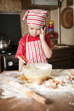 Little chef in the kitchen. Wearing an apron and headscarf Royalty Free Stock Photos