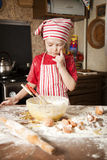 Little chef in the kitchen. Wearing an apron and headscarf Stock Photos