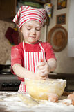 Little chef in the kitchen. Wearing an apron and headscarf Royalty Free Stock Images