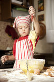 Little chef in the kitchen. Wearing an apron and headscarf Royalty Free Stock Image