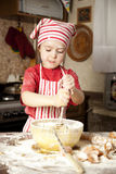 Little chef in the kitchen. Wearing an apron and headscarf Royalty Free Stock Photography