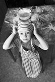 Little chef in the kitchen. Wearing an apron and headscarf Stock Photo
