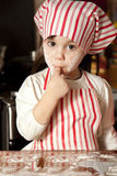 Little chef in the kitchen. Wearing an apron and headscarf Stock Image