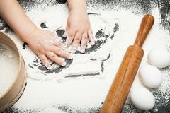 Little chef plays with small hands with flour stock image