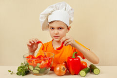 Little chef puts chopped vegetables for salad in a bowl Royalty Free Stock Images