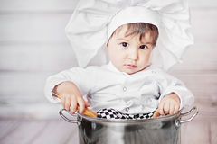 Little chef sitting in big pan. Cute little baby. Funny chef sitting in big pan Stock Image
