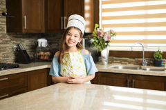 Little chef standing in a kitchen and smiling royalty free stock photography