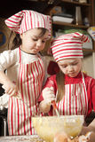 Little chefs in the kitchen. Little chef in the kitchen wearing an apron and headscarf Stock Photos