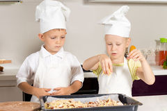 Little Chefs Putting Cheese on Pizza Seriously Royalty Free Stock Images