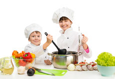 Little chefs by table with vegetables Stock Images