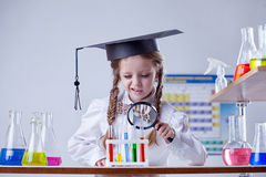 Little chemist looking at tube through magnifier Stock Images