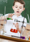 Little chemist pours colored liquid in flask. Little chemist pours colored liquid in conical flask holding an experiment Royalty Free Stock Image
