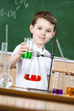 Little chemist shows colored liquid in flask Royalty Free Stock Photo