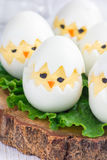 Little chicken in nest, deviled eggs served with salad on board, vertical Stock Photo