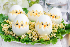 Little chicken in nest, deviled eggs served with salad and dry ramen on plate, horizontal Stock Images