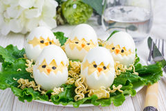 Little chicken in the nest, deviled eggs served with salad and dry ramen on white plate, horizontal Royalty Free Stock Photo