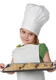 Little chief cook. Little girl with chief hat holding a cookie sheet, isolated on white royalty free stock photography