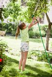 Little child, adorable blonde teen girl, watering the plants, beautiful flowers, from hose spray in the garden. At the backyard of the house on a sunny summer royalty free stock image