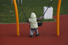 Little child in autumn jackets swinging in a swing his back turned Royalty Free Stock Image