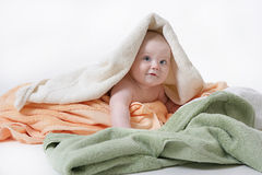 Little child baby. Lying under colorful towels on white background Stock Image