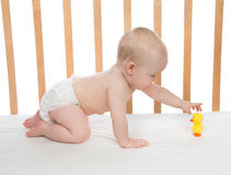 Little child baby girl crawling in bed with toy duck. Little child baby girl crawling in bed with hand trying to hold yellow toy duck in diaper on a white royalty free stock photography
