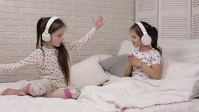 Little child baby girl listening to the music with headphones stock footage
