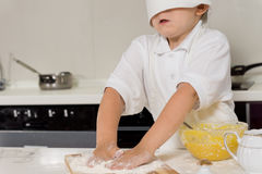 Little child baking in a chefs toque Stock Image