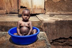 Lille child bathing in a village in Uganda stock images