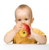 Little child is biting red apple. Cute little child is biting red apple while sitting at table, isolated over white stock photos