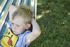 Little child blond  boy swinging and relaxing on a hammock Stock Images