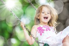 Little child blond girl having fun on a swing Royalty Free Stock Images