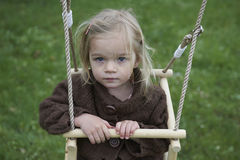 Little child blond girl having fun on a swing outdoor Stock Photo