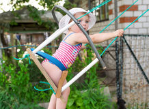 Little child blond girl having fun on a swing outdoor. Royalty Free Stock Image