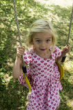 Little child blond girl having fun on a swing outdoor. Summer playground Stock Photos